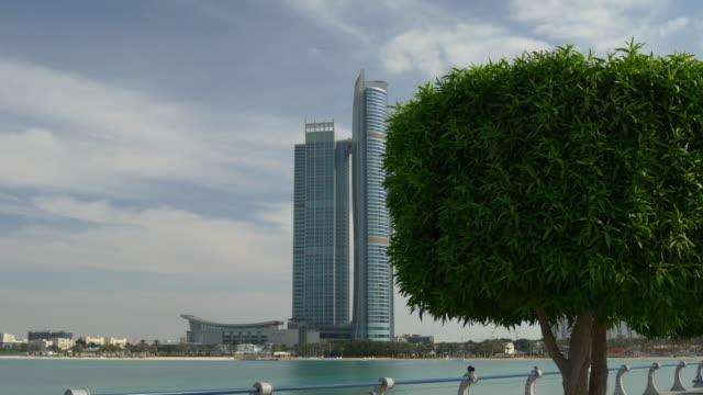 abu dhabi day corniche beach bay nation towers walking panorama 4k united arab emirates - uae national day стоковые видео и кадры b-roll