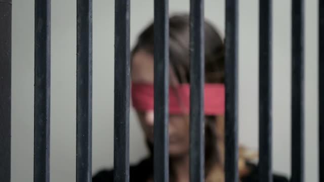 vídeos y material grabado en eventos de stock de abusada a mujer joven encarcelada en una celda, cinta roja de blindfoldedwith - human trafficking