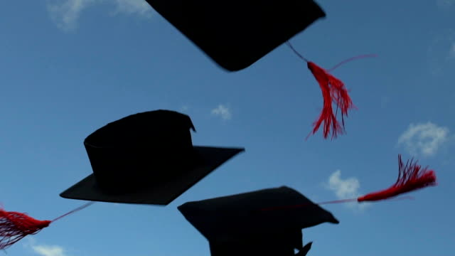 academic mortarboards thrown up in clear blue sky by carefree happy graduates - tocco accademico video stock e b–roll