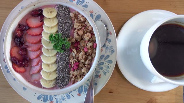 acai berry bowl with fruits and cup of coffee
