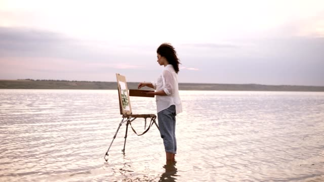 accelerated shooting, a girl artist in the water till ankles draws a landscape using an easel and a palette. curly girl on the background is lake, she's in casual clothes: jeans and a white shirt - painter stock videos and b-roll footage
