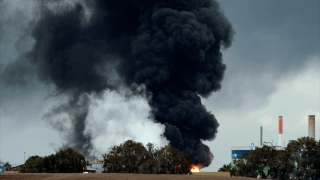 Accident in oil refinery - huge explosions and fireballs rising. Thick black smoke covers the sky. video