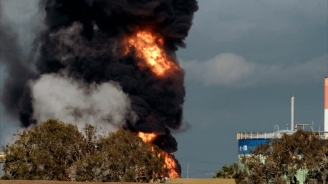 vídeos de stock e filmes b-roll de accident in oil refinery - huge explosions and fireballs rising. thick black smoke covers the sky. - inferno fogo