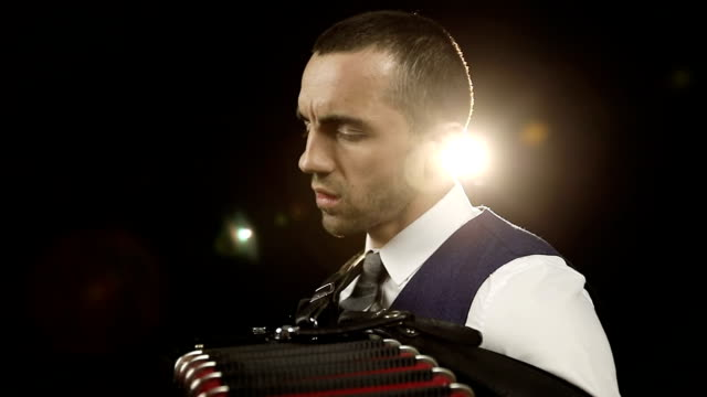 Accordionist in a white shirt and grey tie. video