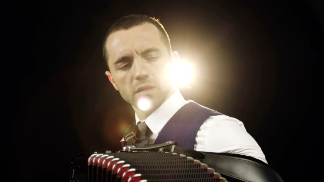 Accordionist in a white shirt is playing the accordion. video