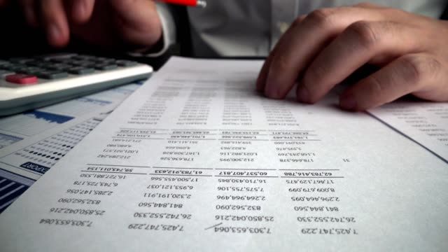 Accountant analyzing business marketing data on paper dashboard at office table. Accountant analyzing business marketing data on paper dashboard at office table. Corporate finance and money accounting concept. bills and taxes stock videos & royalty-free footage