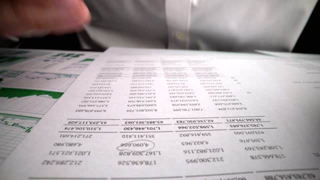 Accountant analyzing business marketing data on paper dashboard at office table.