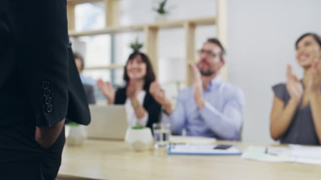 Acknowledging a job well done 4k video footage of a group of businesspeople applauding a colleague while sitting in the boardroom focus on foreground stock videos & royalty-free footage