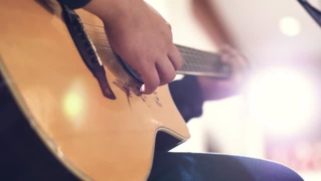 vídeos de stock, filmes e b-roll de guitarra acústica nas mãos do músico na festa. - música acústica