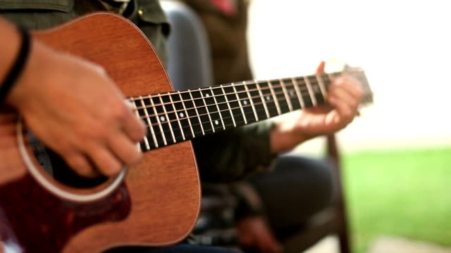 Acoustic guitarist playing chords, close-up video