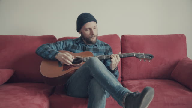 Acoustic guitarist playing guitar on his sofa video