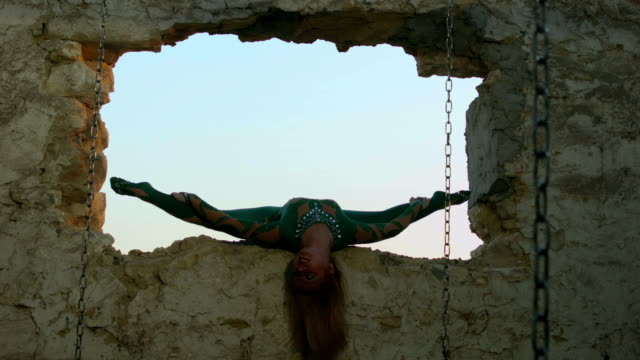 Acrobat exercising in ruined window frame video