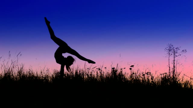 Acrobat girl exercising in the evening field arrow position video