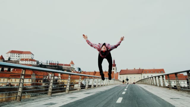 SLO MO Acrobatic breakdancer performing somersaults on the bridge video