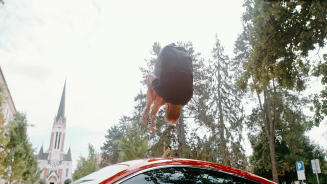 MS Acrobatic teenage boy backflipping over parked red sports car