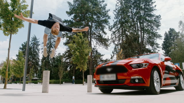 MS Acrobatic young man backflipping in front of parked red sports car