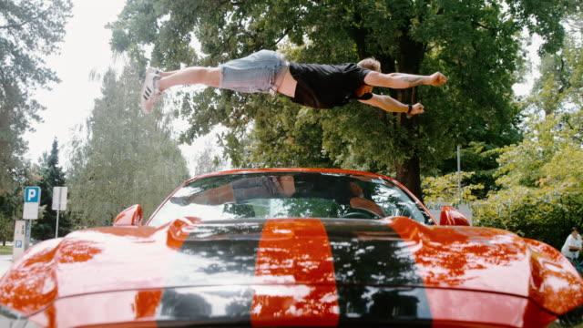 빨간 스포츠 차 ms 곡예 젊은 남자 backflipping - 10초 이상 스톡 비디오 및 b-롤 화면