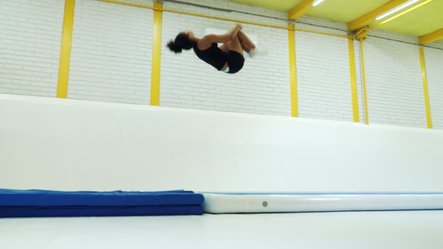 Acrobatics girl practicing somersaults on mats in gym
