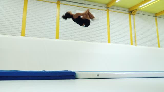 akrobatik flicka tränar kullerbyttor på mattor i gymmet - endast en ung kvinna bildbanksvideor och videomaterial från bakom kulisserna