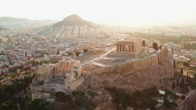 akropol miasta aten partenon, symbol starożytnej grecji, z lotu ptaka slajdów z drona na panoramę budynków mieszkalnych o wschodzie słońca latem. światła słońce, flara obiektywu. światowego dziedzictwa unesco. historia - attyka grecja filmów i materiałów b-roll