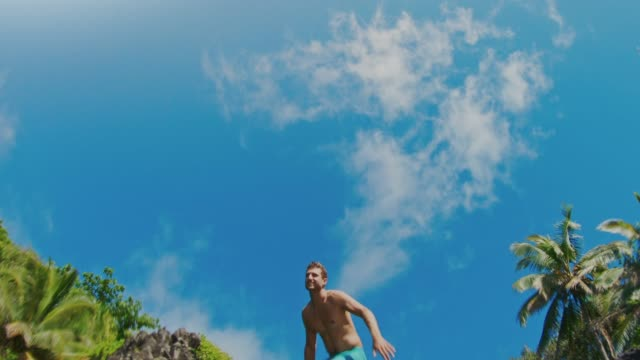 action camera shot of young man jumping into pristine blue water - influencer стоковые видео и кадры b-roll