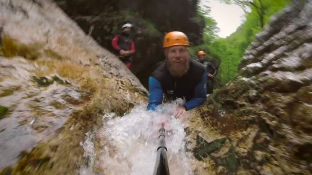 action pov video of man canyoning in the soca valley in slovenia. - slitta video stock e b–roll