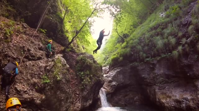 Action video of man jumping into canyon pool in the Soca valley in Slovenia.