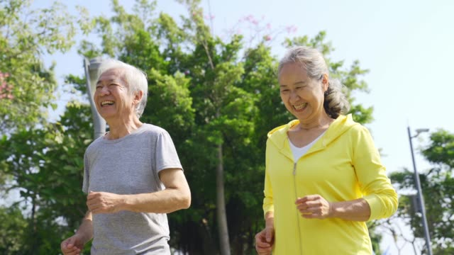 active asian old man and woman jogging outdoors