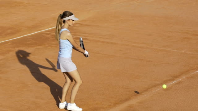 Active beginner tennis player practicing ball return, racket sport, slow motion video