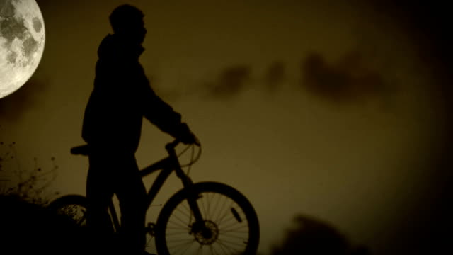 Active biker runs with bicycle in night moonlight