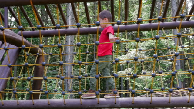 Active boy playing on climbing net at outdoors playground video