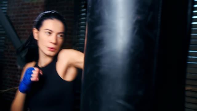 active brunette sportswoman fighting punching bag at loft background medium close-up - sacco per il pugilato video stock e b–roll