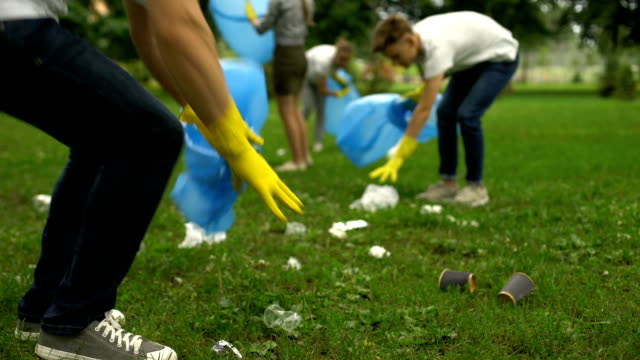 Active citizens collecting garbage in public park, society against pollution