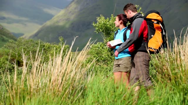 Active couple hiking together and reading map video