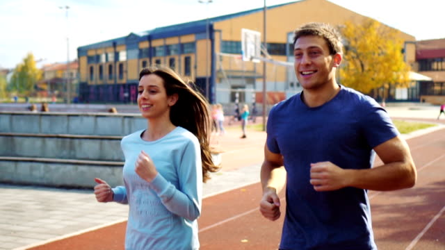 Active couple jogging on athletic track video
