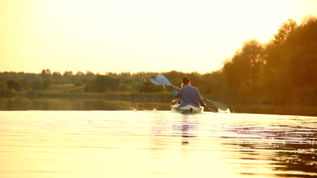 Active couple kayaking at sunset. Healthy way of living, sport video