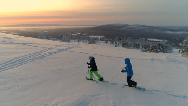 aerial active couple snowshoeing up a mountain slope in snowy lapland at sunrise - дикая местность стоковые видео и кадры b-roll