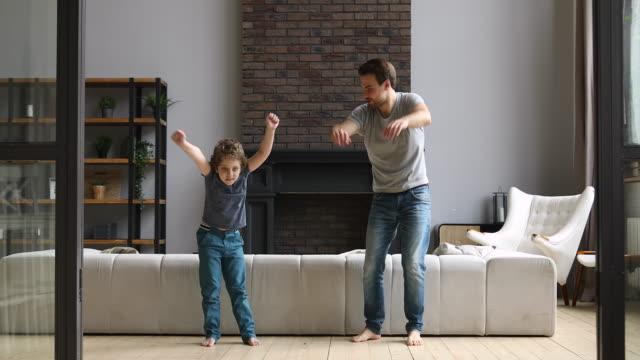 vídeos de stock e filmes b-roll de active dad teaching son doing morning exercise dancing at home - treino em casa