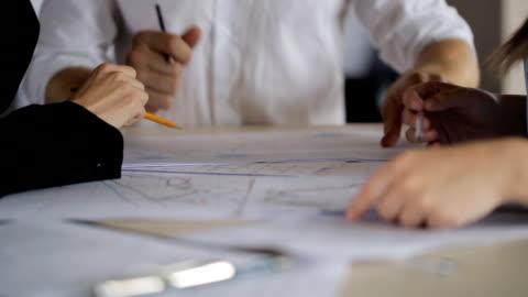 vidéos et rushes de discussion active des diagrammes et des plans sur le papier avec vos mains et crayons derrière un bureau - architecte