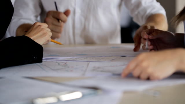 active discussion of charts and plans on paper with your hands and pencils behind a desk - progettare video stock e b–roll