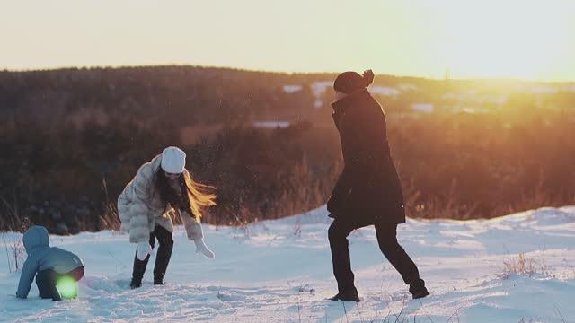 aktive familienmitglieder im winter dressing spielen schneebälle - menschliche beziehung stock-videos und b-roll-filmmaterial