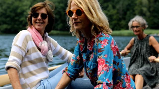 aktive freundinnen genießen boot fahren in see - aktivitäten und sport stock-videos und b-roll-filmmaterial
