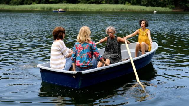 湖でボートを楽しむアクティブな女性の友人が乗る - disruptagingcollection点の映像素材/bロール
