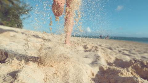 slow motion: una turista attiva fa jogging a piedi nudi lungo la costa di sabbia bianca. - isola video stock e b–roll