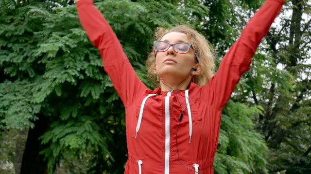 Active fitness woman in red clothes and eyeglasses is stretching outdoor in the park during spring or summer rainy morning. Healthy lifestyle concept