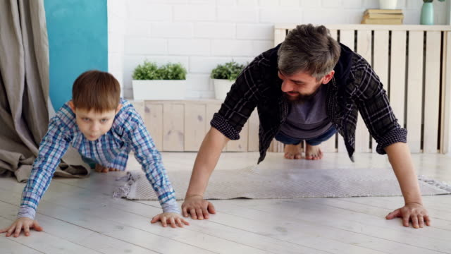 Active handsome father and his joyful son are exercising doing press-up together at home on wooden floor. Happy family, sport and sporty lifestyle concept. Active handsome father and his joyful little son are exercising doing press-up together at home on wooden floor. Happy family, sport and sporty lifestyle concept. push ups stock videos & royalty-free footage
