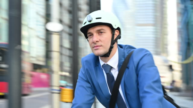 Active male executive in early 30s cycling in City of London
