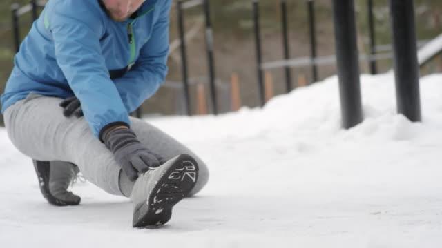 aktiv man stretching ben utomhus på vintern - balettstång bildbanksvideor och videomaterial från bakom kulisserna