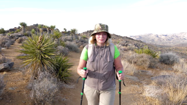 Active Mature Woman Hiking On the Trail Is In the Mojave Desert, Front View video