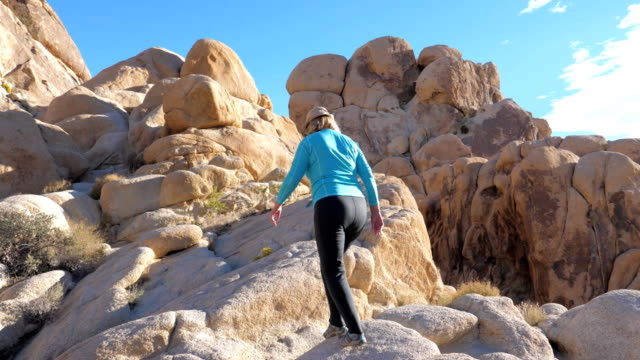 Active Mature Woman Walking And Climbing Up The Rocky Stones Sandy Color video